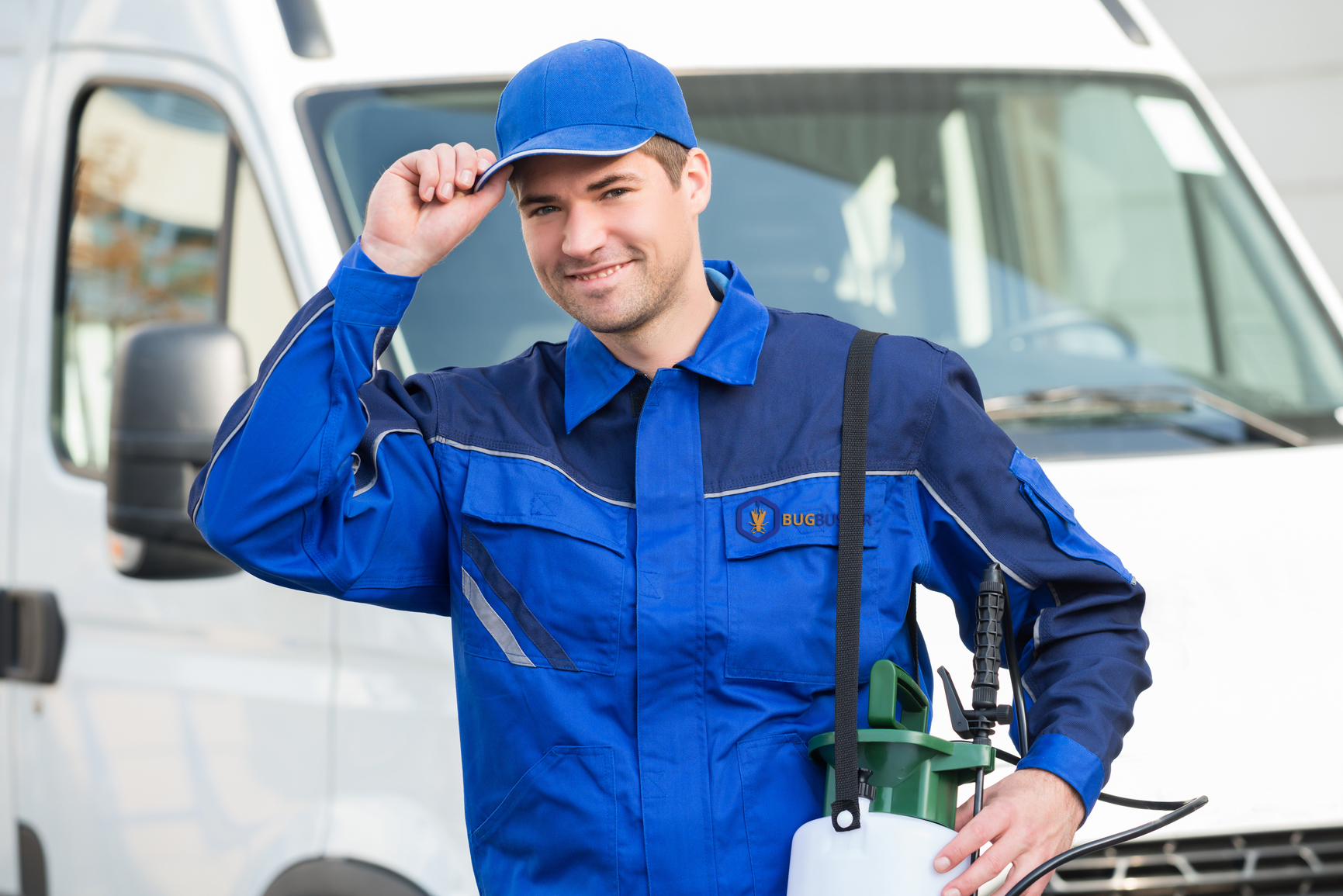 Portrait of confident pest control worker wearing cap against truck